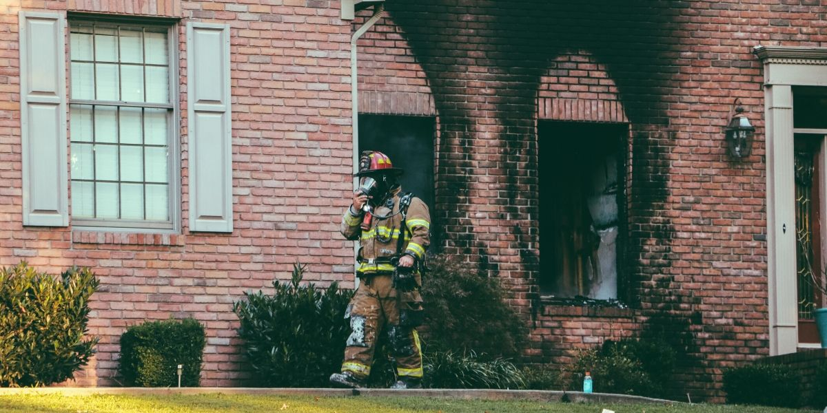 Fireman walking away from house after a fire